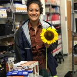 woman holding a sunflower in pantry behind donations