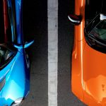 orange and blue cars in parking spaces