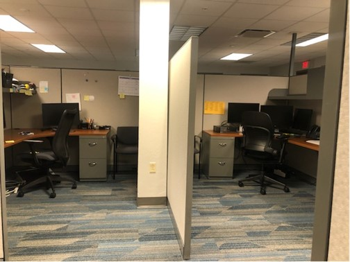 Tall barriers, at least 6 feet between desks, and desks face away from each other.